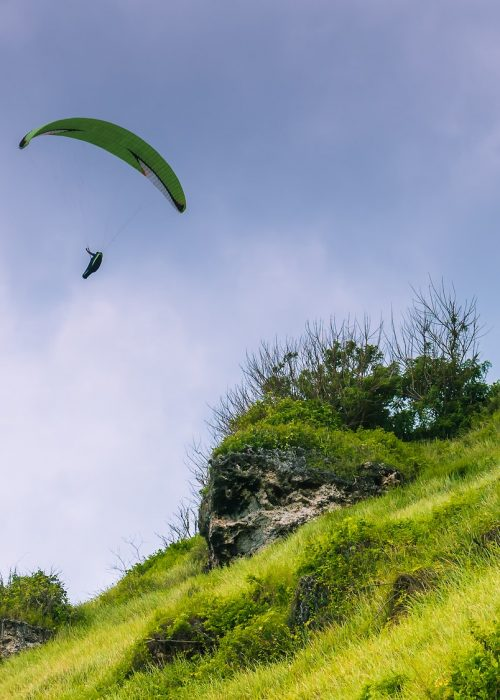 Paraglider flying off the Grassy Hills above Gunung Payung Beach, Bali